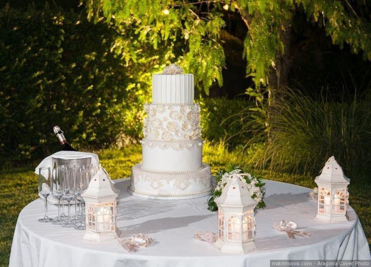 Decorazioni con piccole lanterne bianche sul tavolo esterno per la torta nuziale. Illuminazione d'esterni come decorazione del banchetto di nozze