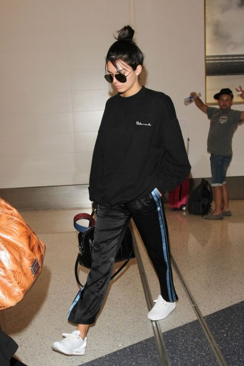 Kendall Jenner gives us stylish lax wear with track pants and hang bag with simple black shades.