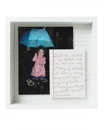 Daisy's First Day of School  Daisy's first day of school -- umbrella, galoshes, and all -- is remembered with this enlarged photo and note, both mounted on foam board. The background paper is lined to mimic loose-leaf paper's classic design.