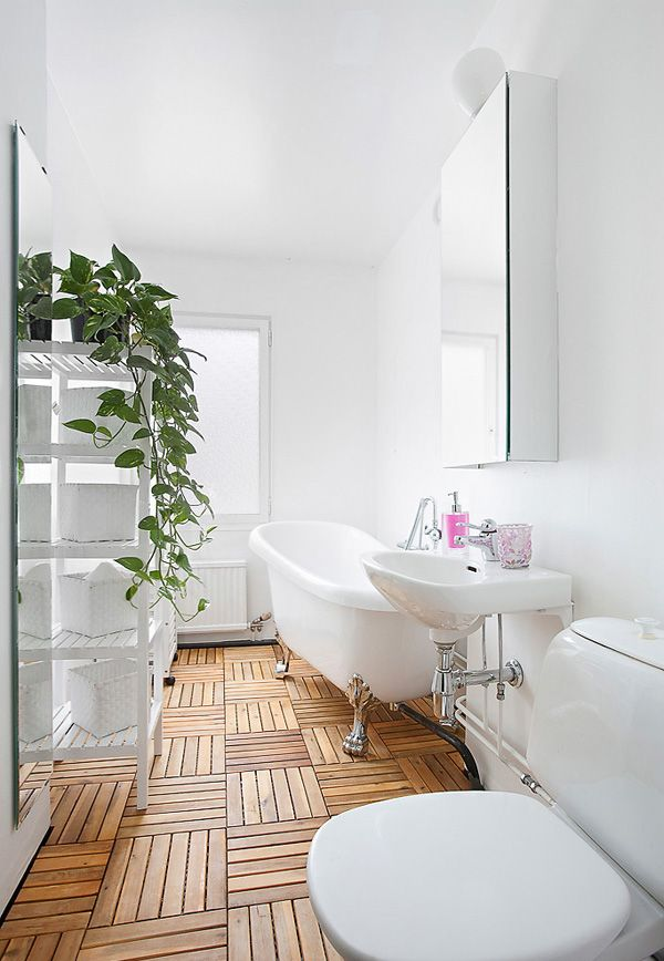 A modern bathroom in all white w/ wood floors is an elegant interior design choice. Complete w/ a clawfoot tub & indoor plants, this bathroom is so bright & vibrant!