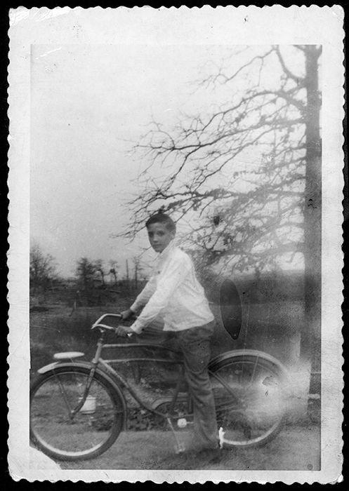 Elvis sur son nouveau vélo à Tupelo autour de Janvier, 1948. | Elvis a reçu un vélo Firestone pilote classique, le plus probable pour son 13e anniversaire. En 1993, une photo a été trouvée dans le placard de Gladys à Graceland d'Elvis sur un nouveau vélo avec «13 ans» écrit sur le dos.