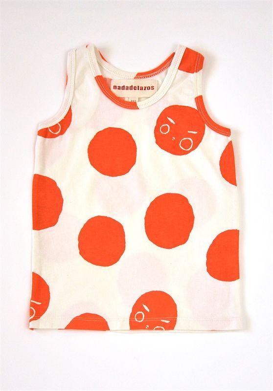Τοπ σε λευκό χρώμα με τυπωμένους κόκκινους ήλιους.  Από 100% οργανικό βαμβάκι.  Κατασκευή: Ισπανία