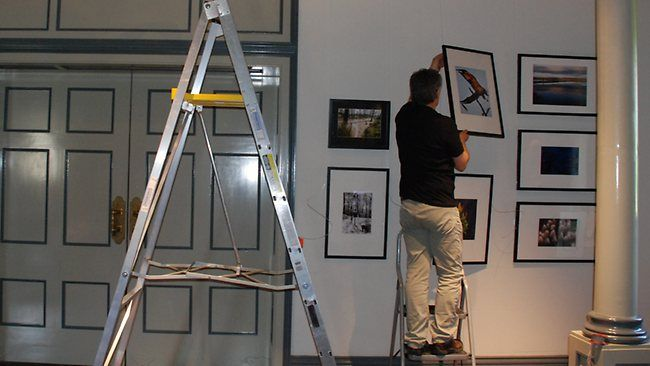 Port Arthur Historic Site staff member Michael Smith hanging works for the Out of the Ashes exhibition.