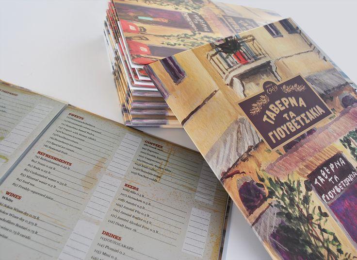"""Σχεδιασμός και εκτύπωση menu για τη ταβέρνα """"Τα Γιουβετσάκια"""" στη Πλάκα.  Σκληρά εξώφυλλα λαμιναρισμένα σε χαρτόνι 2mm και αποσπώμενα φύλλα Α4 που συγκρατούνται με αμφικόχλιες μπρούτζινες διακοσμητικές βίδες."""