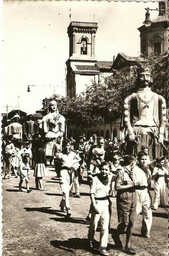 San Fermín. Comparsa de Gigantes y cabezudos seguida por la gente. Al fondo, la iglesia de San Lorenzo, donde se encuentra la capilla de San Fermín, patrón de Pamplona.