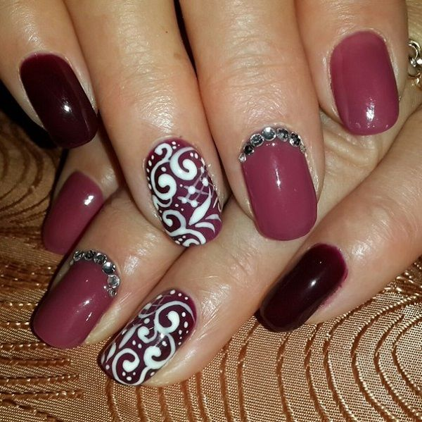Tribal inspired white and maroon nail art design. The nails have a maroon polish as the base color while the various tribal inspired designs on top are painted with white polish.