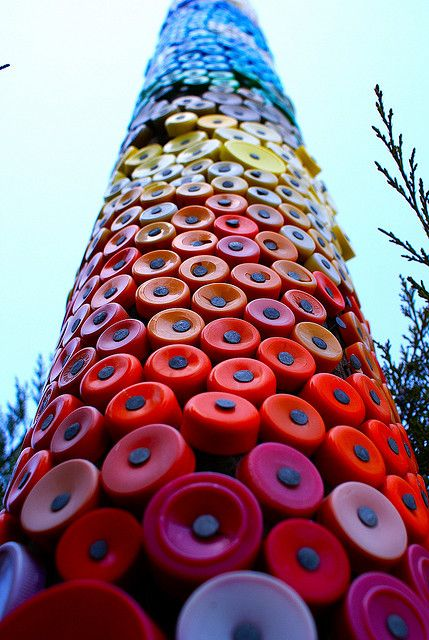 A tall pole with lots and lots of plastic bottle caps nailed into it. From the Dick and Jane Art Spot in Ellensburg WA.