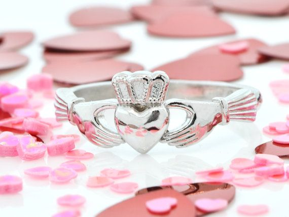A classic sterling silver Claddagh ring. The Claddagh ring features two hands holding a center heart, the gesture of clasped hands is a symbol of pledging vows, and they can be used as engagement/wedding rings or promise rings. These elements symbolize the qualities of love (the