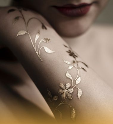 See more Golden flower leaves tattoos on arm