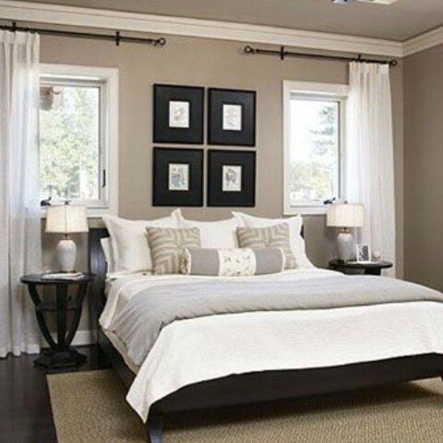 Quarto de casal com paredes creme/bege, quadros pretos e mesa lateral em madeira embuia. Piso escuro e cortinas brancas. Tapetes claro.