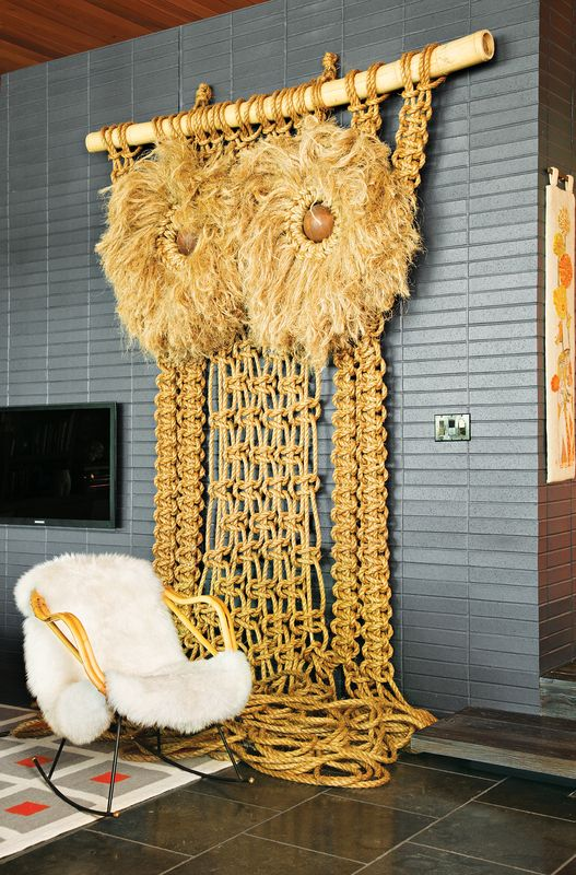 """Andy Harman's macramé Owl punctuates the living room with a California-craft sensibility while the midnight-blue brick imbues the space with a """"German-Brutalist-1960s kind of feel,"""" says Adler. """"It gives the room a nice architectural gravitas."""""""