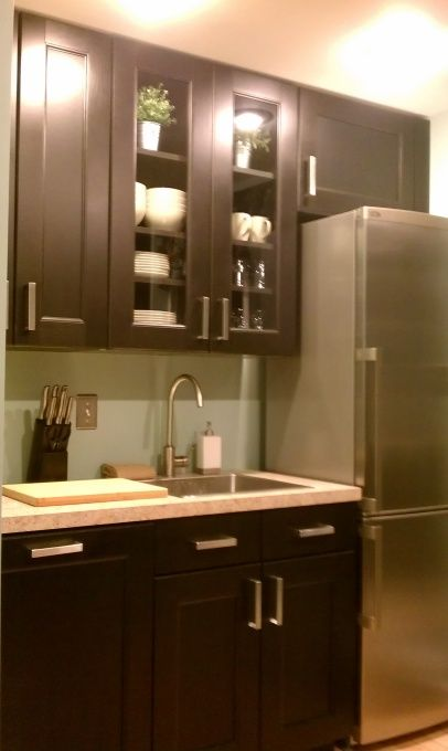 Think of the basement. Move the fridge on another wall.  These are Ikea cabinets.  I like that some are glass to give depth.