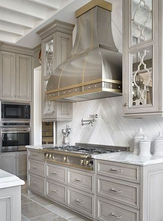 Gorgeous grey washed kitchen and stainless hood with brass details.  Cabinets with mirror inlays