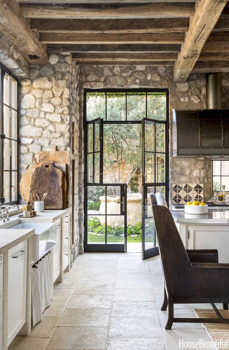 stone wall in kitchen with steel french doors
