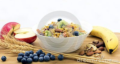 Wholegrain breakfast cereal, sliced kiwifruit and blueberries in a white bowl against a white background. A banana, apple halves, wheat, nuts and blueberries surround the bowl.