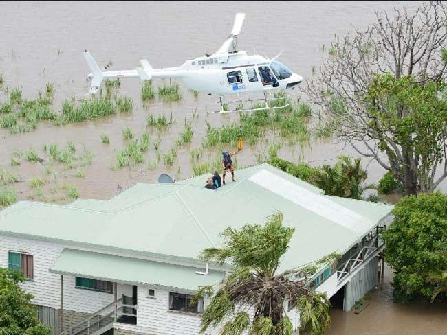 A couple are winched to safety from the roof of their house in Bundaberg. Picture: Paul Beutel
