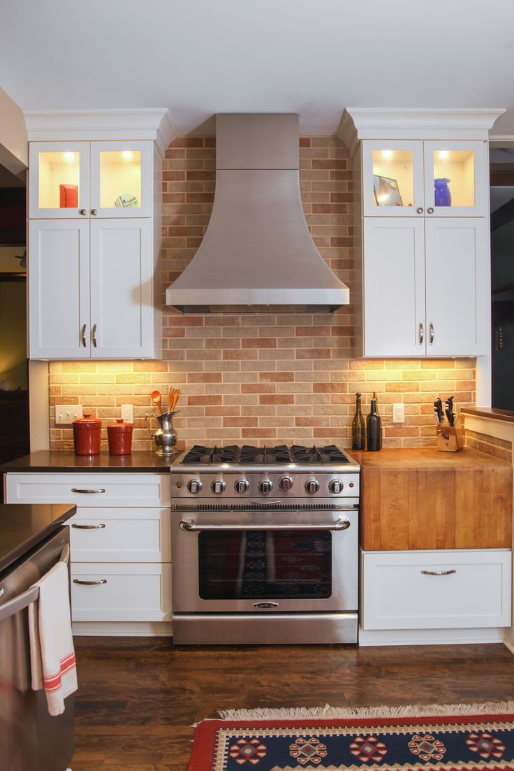 glass cabinetry with stainless steel hood and brick tile transitional kitchen cabinets painted in white: kitchen cabinets home office transitional