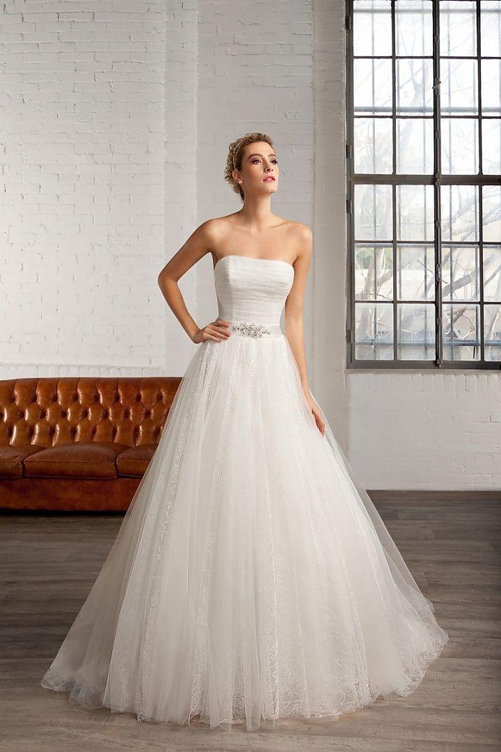 7755, collectie 2016 Een prinsessen trouwjurk zoals die moet zijn; met een glad lijfje en een wijde aangerimpelde rok van fijne kant. De band met applicatie benadrukt de taille extra. #strapless #ivoor #koonings