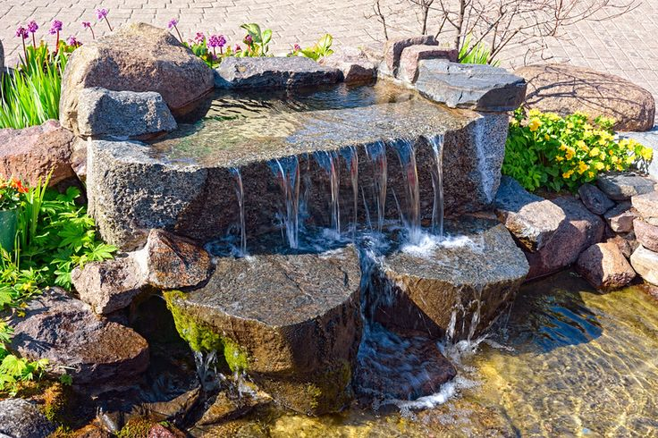 Water garden with waterfall and pond surrounded by green foliage and flowers.