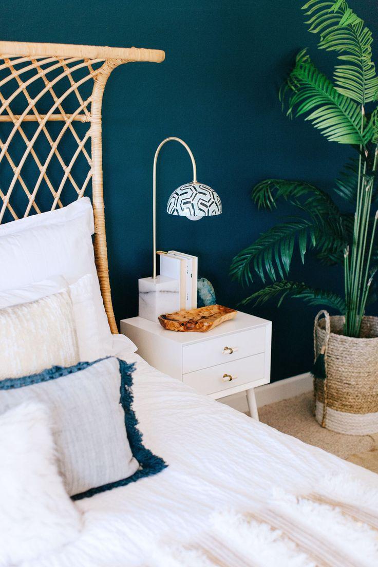 Ambiance moderne et nature dans cette chambre aux murs bleu canard, en associant un lit en osier et une belle plante imposante.