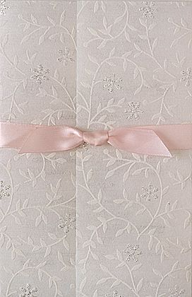 These wedding invitations consist of an inner printed card and a glitter paper wrap. The whole thing is surrounded by a pre-tied ribbon. www.kardella.com