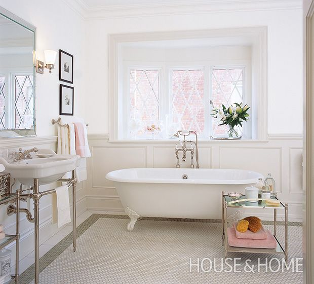 Cloud White lends this bathroom a calming palette that's warmed by panelled wainscoting (in Benjamin Moore's Chantilly Lace). Thassos tiles blanket an area of the floor in a classic hexagonal mosaic that creates the feel of a rug. | Photographer: Ted Yarwood | Designer: Jennifer Worts