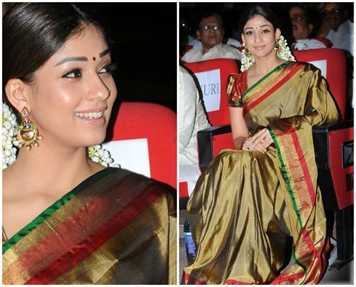 Nayantara in a beautiful Khaki color soft silk saree teamed up with red & gold silk outlines and gold hand loom border with running pallu. The actress paired it with contrast red raw silk puffed sleeves designer silk blouse & crew neck pattern.