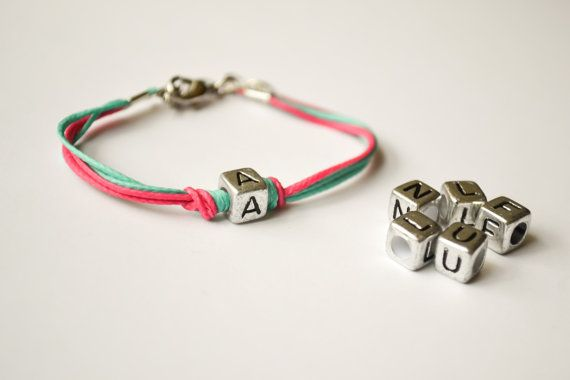 Initial charm bracelet - Cord Bracelet with a Tibetan silver english letter charm. The cords are bright pink and turquoise and made of wax and the