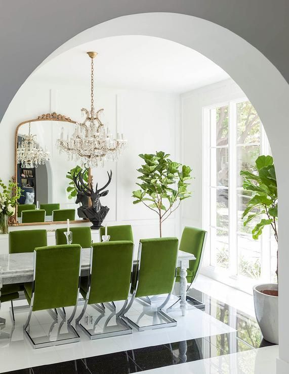 Contemporary dining room features a crystal chandelier hanging above a white marble dining table lined with apple green velvet dining chairs atop a black and white tiled floor.