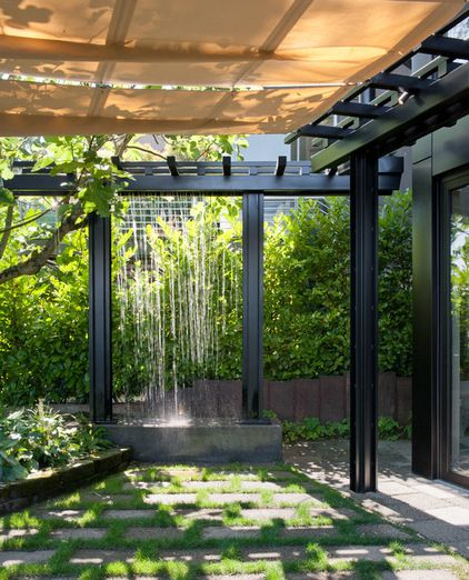 """In addition to being a green component, the water feature creates a lovely ambiance for the backyard and nearby rooms.  """"The house is close to a floating bridge, which is loud,"""" says Castanes. """"This mitigates those sounds with a much more pleasant white noise."""""""
