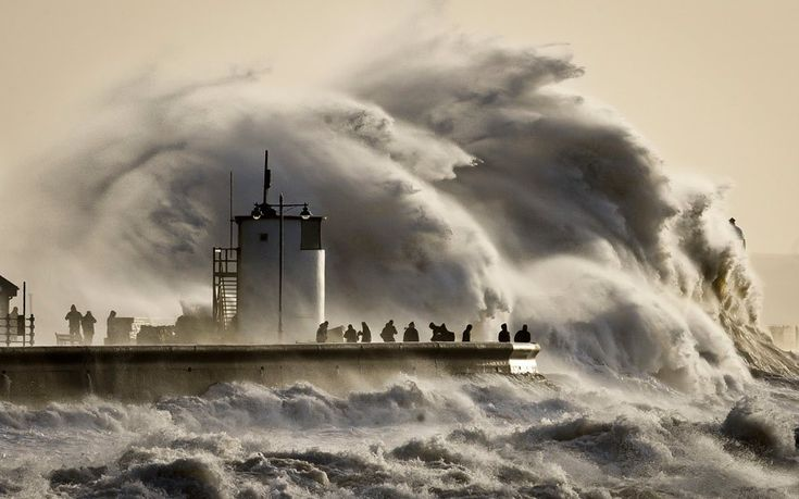 People watch and photograph enormous waves as they break on Porthcawl harbour in South Wales
