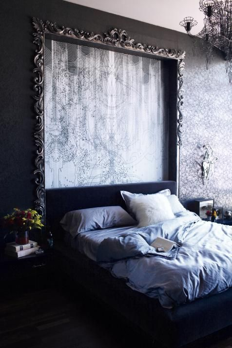 "The aesthetic in this modern bedroom is ""rock star gothic grunge with a modern twist."" Custom mural wallpaper by Iris Maschek is recessed into an illuminated cove and framed with a custom silver leaf frame by Voila Gallery, becoming artwork in the space. The neo-Baroque Abigail Ahern light fixture above the bed is a masterpiece on its own."