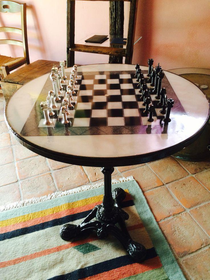 Scacchiera realizzata con mattonelle stuccate con piombo sotto uno strato di resina e scacchi realizzati con varia bulloneria.