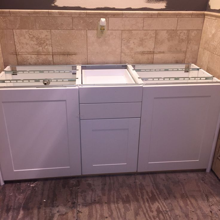 Bathroom remodel using IKEA kitchen cabinets. Just build a frame to raise to the perfect height and add molding to cover the spaces.