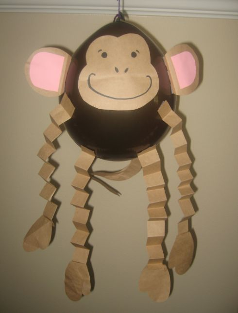 Monkey balloons for a safari or jungle themed birthday party.  Brown balloons from the party store.  Parts cut from brown paper grocery bags and pink construction paper.