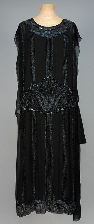 CHIFFON DINNER DRESS with IRIDILL BEADS, c. 1920 Sleeveless black silk with beaded vertical bands, heavily decorated at the neckline and midriff with chamfered beads in two sizes, side drape, silk under-dress. B-44, L-50. (Several small light spots on bodice) very good.