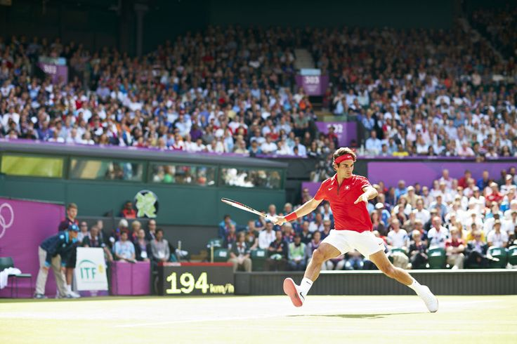 London 2012 - Switzerland's Roger Federer leaps to return a shot during his Olympic tennis men's singles gold medal match with Andy Murray of Team GB at Wimbledon.  IOC / John Huet