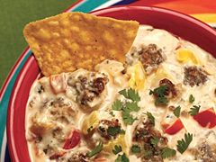 ZESTY FIESTA SAUSAGE DIP  1 package (16 oz.) Jimmy Dean® Regular Flavor Pork Sausage Roll  1 large onion chopped  1 large red bell pepper, chopped  1-2 jalapeno peppers, seeded, chopped  2 pkgs. (8 ounces each) cream cheese, cubed  1 large tomato, seeded, chopped  ½ cup hot yellow banana peppers, drained, seeded, chopped  ⅓ cup chopped fresh cilantro