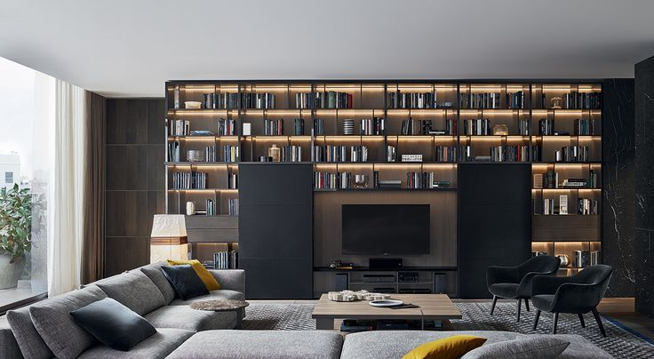 """Wall System, moka glossy lacquered, back panels and Flat drawers in cenere oak, Bold sliding doors in black hide and guide rail moka mat lacquered, inner grid th. 1/2"""" moka mat lacquered. Bristol sofa in 412 cemento Rabat removable fabric, cushions in 1403 ocra and 1404 carbone Persia velvet. Bristol coffee table in cenere oak. Mad Chair armchairs with legs in spessart oak and body covered in 1404 carbone Persia removable velvet."""