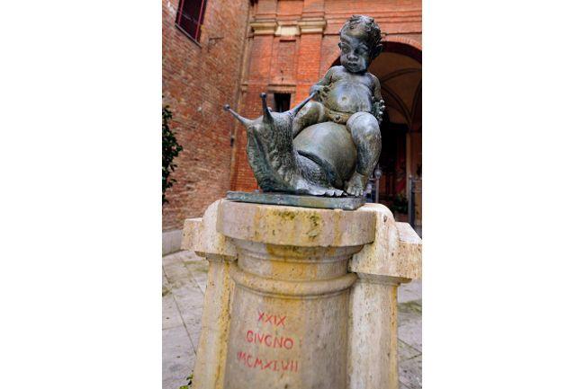a statue of a young child and a snail within the Contrada della Chiocciola