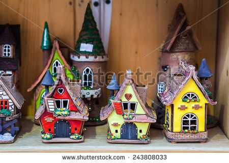 A clay houses stands over a wooden background - stock photo