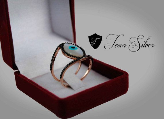 925 Silver Handmade  Evil Eye Charm Ring  The Evil Eye stone in the Middle is a Mother of Pearl  The Black Side stones are Swarovski  The Whole ring is plated with Rose Gold  Don't forget to pick your Finger Size (Ring Size) before you put this item in your shopping cart.  If you can't find your size in the list provided please contact us after the purchase.  ___________  You will recieve your lovely ring in it's special gift box, among with other gifts.  __________  We offer Free…