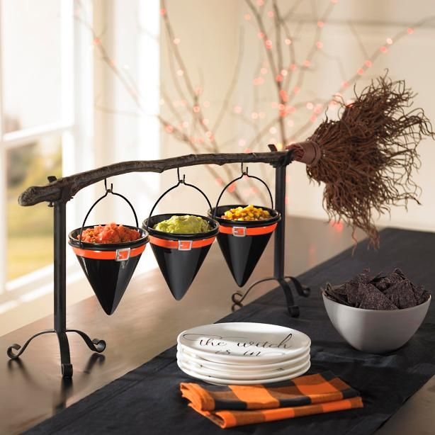 Clever girl, putting that broom to work when you're not running errands. Our Broomstick Snack Bowl Stand is a witching wonder, so handy in so many ways. At nearly 3 ft. long, this is a serving piece to be seen. Cast iron broom handle sits in a stand (also cast iron) and features realistic plastic bristles and three hooks. Use hooks to hang chalkboard-style sign for sketching out a fun greeting or directing guests to snacks; or use them to hang three ceramic, hat-shap...
