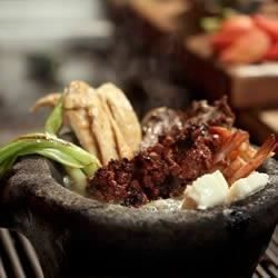 This mixed grill of carne asada, nopales, chicken, shrimp, jalapenos, and chorizo sausage is served in a heated molcajete with queso fresco, salsa, avocado and lime for a delicious Mexican feast.