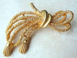A large vintage bow and tassel brooch manufactured by W A P Watson, under the Exquisite brand.  Designed as a triple bow with two tassel detailed ends, in textured and polished gold tone metal  Circa 1960's - 70's.