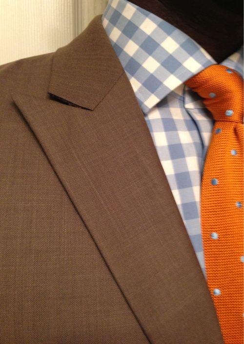 Brown jacket, light blue gingham shirt, orange tie