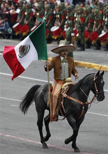 "A man, dressed as a ""Charro"", marches holding a Mexican flag during the Independence Day parade in Mexico City's Zocalo Plaza (AP Photo/Eduardo Verdugo)"