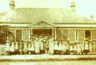 Brisbane Girls Grammar at Wickham Terrace 1875.    The house on Wickham Terrace was owned by the Hon John Douglas, a Grammar School Trustee. The house was a shuttered single storied wooden building, described as having a wide hallway, with two large rooms either side. Wide latticed front and side verandahs and a wide back verhandah leading to two large wings.