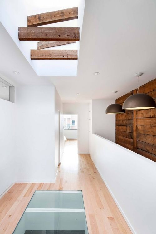 Roof light looks as if it's cut through conventional trusses, flooding stairwell with light which is transferred to floor below via a glazed floor