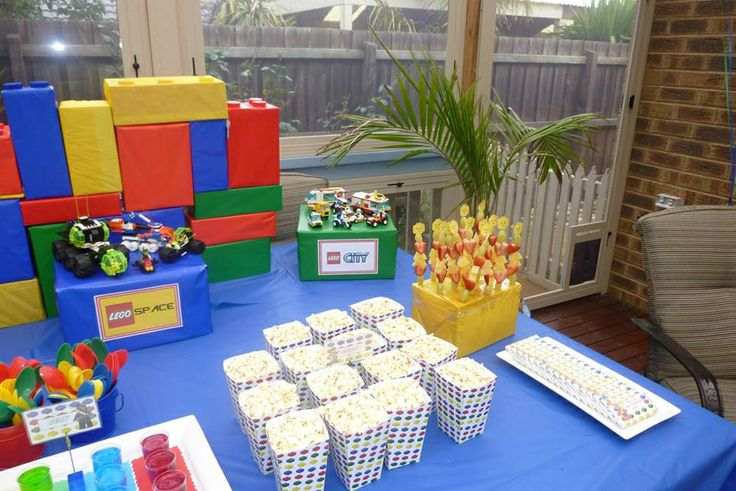 Large LEGO blocks were various size boxes wrapped in gift wrap or tissue paper. LEGO series were displayed on a box.